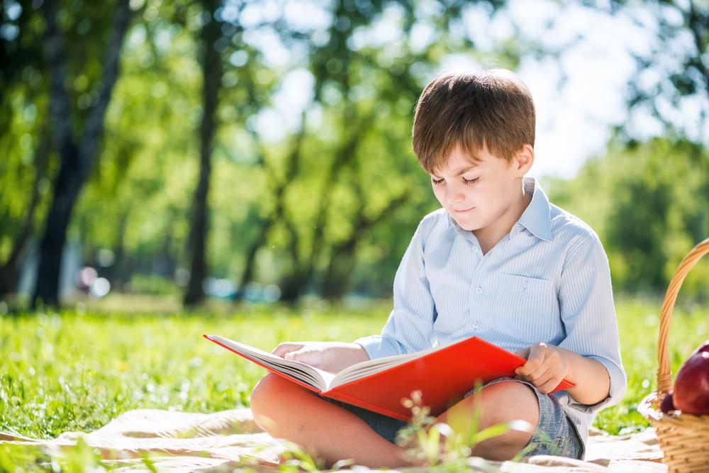 Ce jeune garçon révise ses mathématiques avec les cahiers de vacances